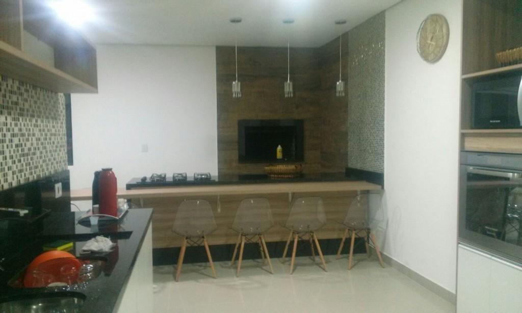 Uma moderna churrasqueira, ao fundo, tem à sua frente a ilha gourmet com fogão e bancada acoplados, além de modernas cadeiras em acrílico. Na parede à direita, o forno de microondas.