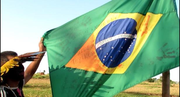 O líder Guarani/Kaiowá, Kunumi Apyka Rendy's (Elson Canteiro Gomes) segura a bandeira do Brasil manchada com sangue dos índios derramado no ataque de produtores rurais que matou o índio